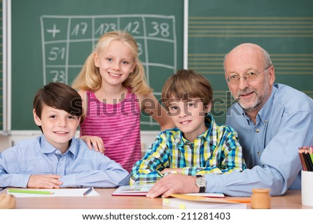 Smiling young boys and a girl in class with their male school teacher all sitting at a desk in front of the blackboard as they discuss class notes - stock photo