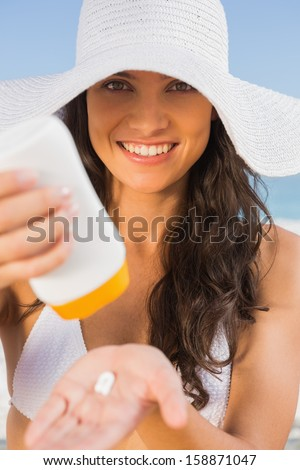 Smiling young brunette on the beach taking care of her body putting on sun cream - stock photo