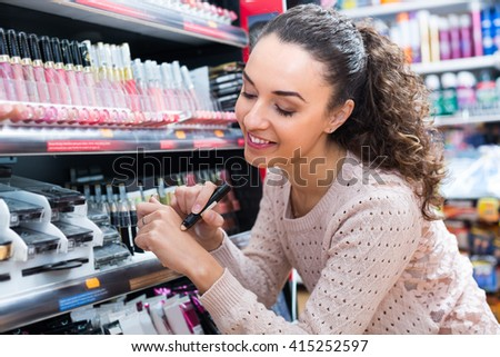Smiling young brunette selecting beauty treatment in makeup section  - stock photo
