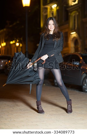Smiling young brunette wearing black clothes posing with umbrella - stock photo