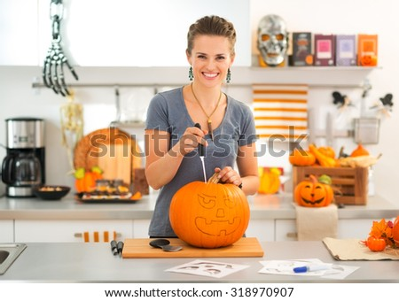 Smiling young brunette woman carving a big orange pumpkin Jack-O-Lantern for Halloween party - stock photo