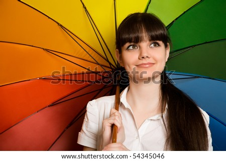 smiling young brunette woman in white blouse with multi-coloured umbrella - stock photo