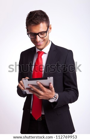 smiling young business man browsing on his new tablet pad - stock photo