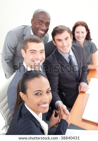 Smiling young business team in a meeting shaking hands - stock photo