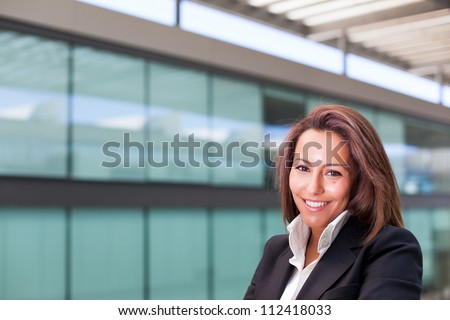 Smiling young business woman at the office - stock photo