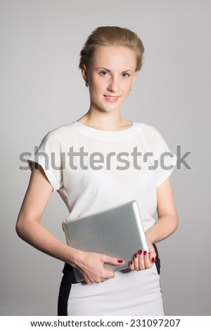 Smiling young business woman holding a tablet PC - stock photo