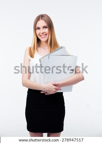 Smiling young business woman holding folders isolated on a gray background. Looking at camera - stock photo