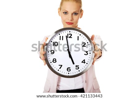 Smiling young business woman holding office clock - stock photo