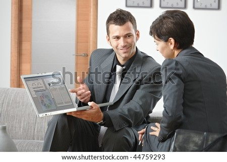 Smiling young businessman presenting on laptop computer sitting on sofa at office. - stock photo