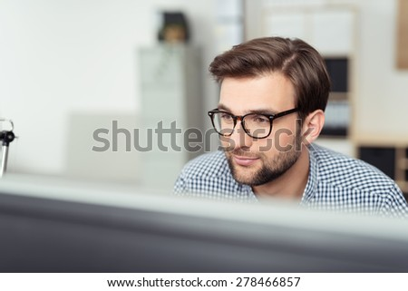Smiling Young Businessman with Eyeglasses Sitting at his Desk and Facing at the Computer Screen, Captured in Close up. - stock photo