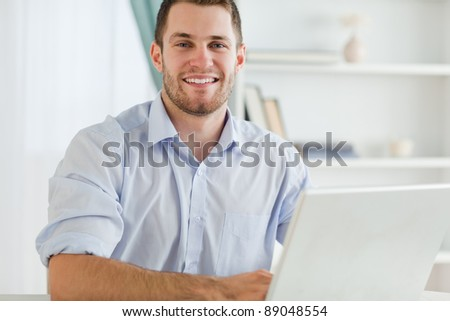 Smiling young businessman with rolled up sleeves in his home business - stock photo