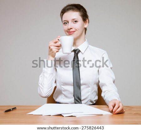 Smiling young businesswoman  holding a cup of tea on workplace, neutral background - stock photo