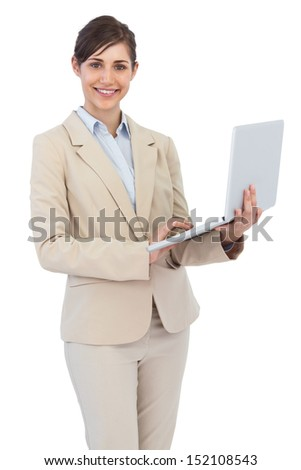 Smiling young businesswoman holding laptop against white background - stock photo