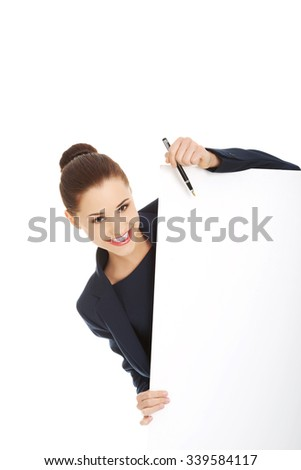 Smiling young businesswoman showing blank signboard - stock photo