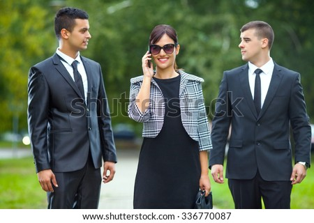 Smiling young businesswoman talking on the phone while walking on the street with two businessmen  - stock photo