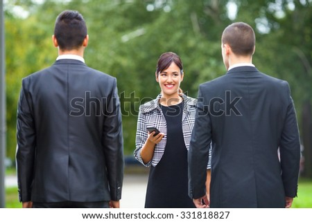 Smiling young businesswoman using mobile phone while meeting two businessmen on the street - stock photo
