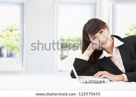 smiling young businesswoman with laptop in the office - stock photo