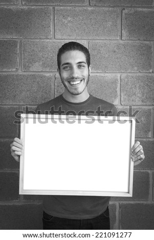 Smiling young casual man holding white sign to write it on your text. Black and white image, brick wall background. - stock photo
