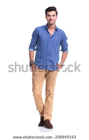 smiling young casual man standing with hands in his pockets on white background - stock photo