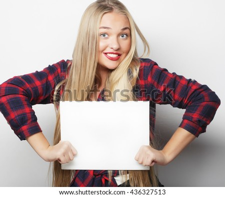 Smiling young casual style woman showing blank signboard, over white background isolated - stock photo