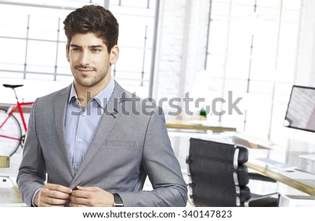 Smiling young caucasian man leaving office. - stock photo