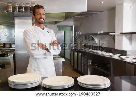 Smiling young chef standing with arms crossed behind counter in a commercial kitchen - stock photo