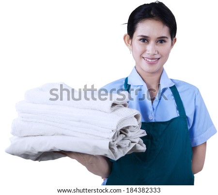 Smiling young cleaning lady holding towels isolated on white - stock photo