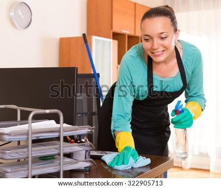 Smiling young cleaning woman wiping the table at office room