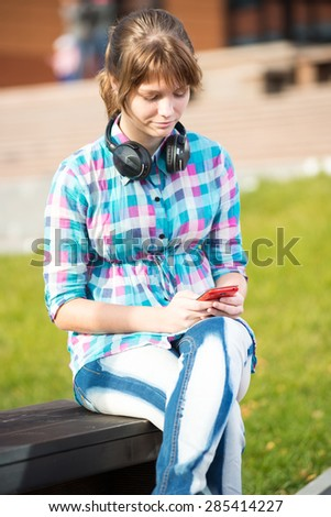 Smiling young college girl texting on a cell phone. Teenage woman using cell phone at campus - stock photo