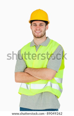 Smiling young construction worker with folded arms against a white background - stock photo