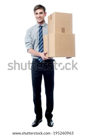 Smiling young corporate man holding stack of boxes - stock photo