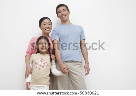 Smiling Young couple and daughter family portrait, low angle view - stock photo
