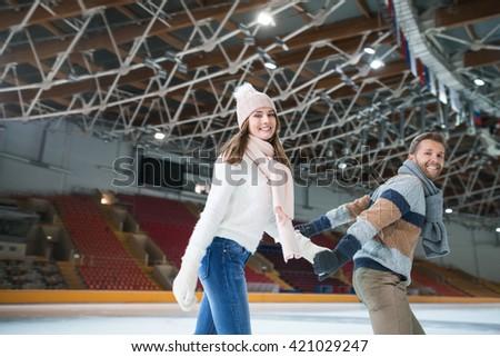 Smiling young couple at skating rink - stock photo