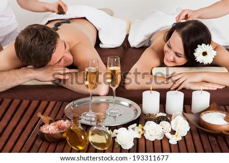Smiling young couple enjoying hot stone massage at beauty spa - stock photo