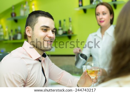 Smiling young couple having a date with wine at bar. Focus on man - stock photo