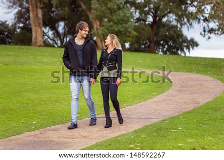 Smiling young couple holding hands walking in a park's path - stock photo