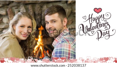 Smiling young couple in front of lit fireplace against happy valentines day - stock photo