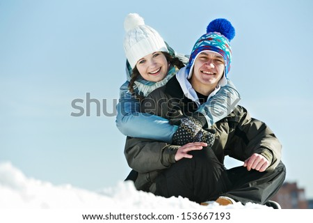 Smiling young couple in warm clothing on snow at winter outdoors - stock photo
