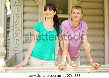 Smiling Young couple leaning on terrace of wooden village house, focus on wife - stock photo