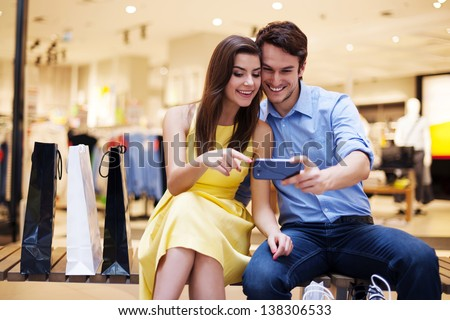 Smiling young couple looking at mobile phone - stock photo