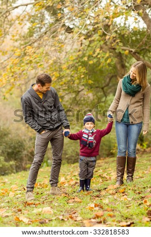 Smiling young couple looking their little boy on an autumns day - stock photo