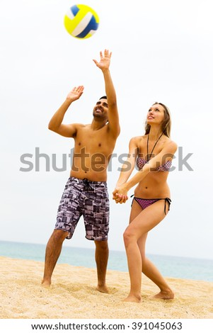 Smiling young couple playing volleyball on the beach. Focus on the woman - stock photo
