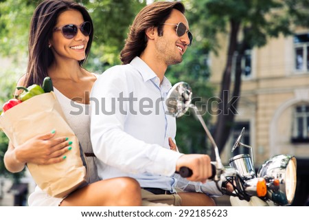 Smiling young couple riding a scooter while woman holding a shopping bag full of groceries - stock photo