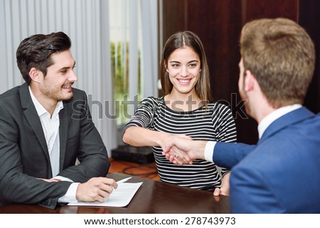 Smiling young couple shaking hands with an insurance agent or investment adviser - stock photo