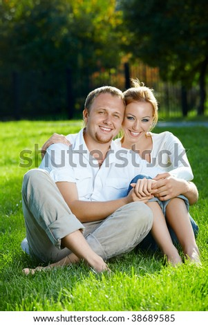 Smiling young couple sits on a lawn in a summer garden - stock photo