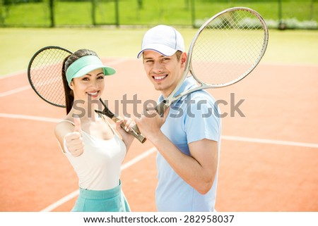 Smiling young couple standing on tennis court, holding tennis racket. - stock photo