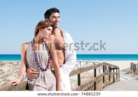 Smiling young couple staying together at summer beach - stock photo