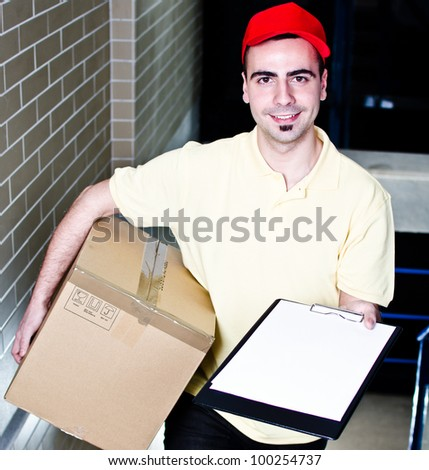 Smiling young courier with package and blank clipboard - stock photo