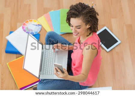 Smiling young creative businesswoman holding a smartphone - stock photo