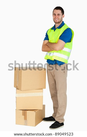 Smiling young delivery man with arms folded against a white background - stock photo